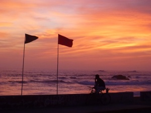 Barranca at sunset. The left flag shows water quality is good, the right flag says no swimming due to turbulence.