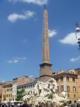 """This obelisk was brought to Rome by Domitian (emperor 81-91 AD). He had hieroglyphs carved on it in praise of himself his father and brother. It eventually lay abandoned in 5 pieces in the Circus of Maxentius on the Appian Way. Pope Innocent X wanted it to top a massive fountain in Piazza Navona, as it now stands. There is a good story about how Bernini gained the commission to create the """"Fountain of the Four Rivers"""" that forms the base of the obelisk (1648)."""